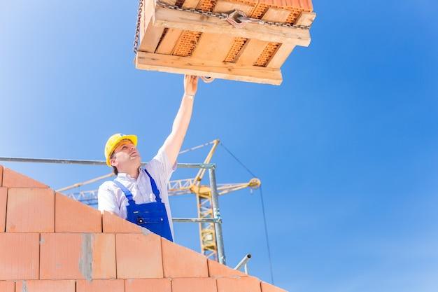 Muratore o operaio edile che riceve una consegna con un pallet di mattoni o pietre dal gruista in costruzione o in cantiere per muri