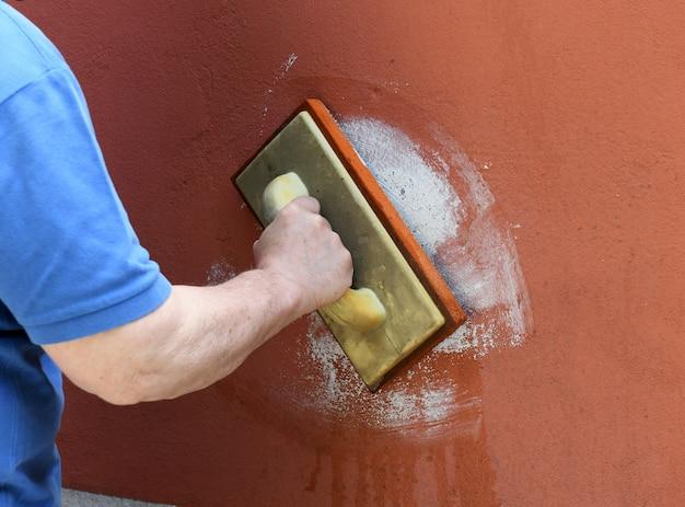 Muratore stuccatura di murature su una parete colorata