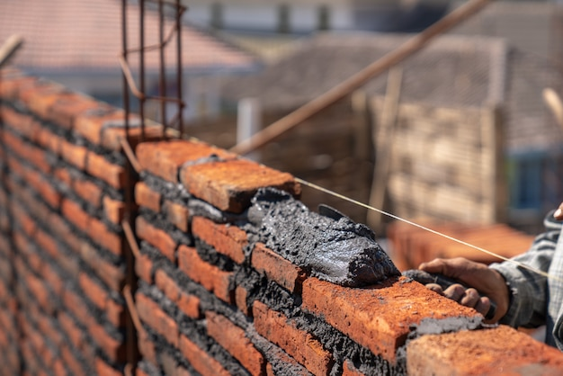 Lavoratore industriale del muratore che installa la muratura del mattone con il coltello di mastice della cazzuola al cantiere