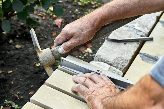 Muratore che installa mattoni sulla nuova recinzione da mattoni faccia a vista usando un martello