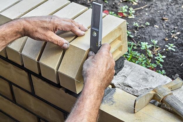 Muratore che livella i mattoni sulla nuova recinzione dai mattoni faccia a vista utilizzando il livello di costruzione