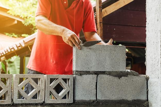 Uomo del muratore che lavora costruire per la costruzione a casa
