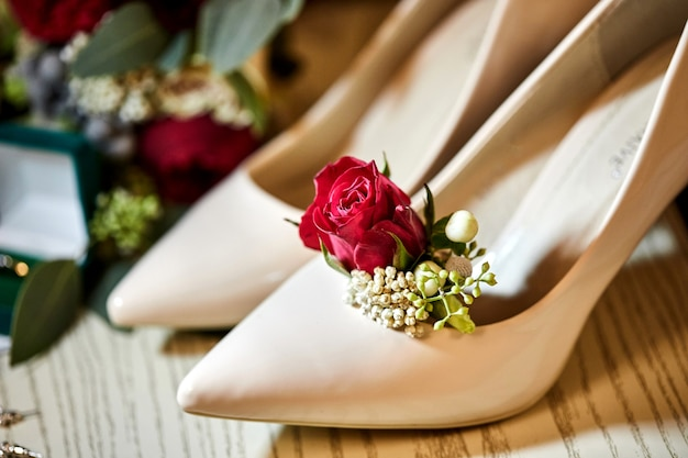 Gli accessori nuziali come scarpe, bouquet, anello e profumo giacciono su un tavolo