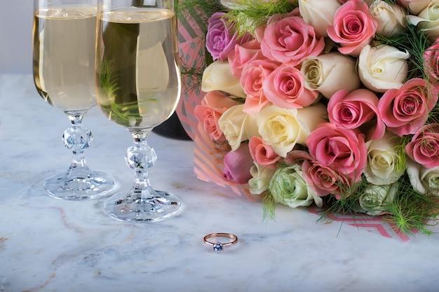 Un bouquet da sposa di rose delicate e anello con un diamante due bicchieri di champagne prima del matrimonio di san valentino
