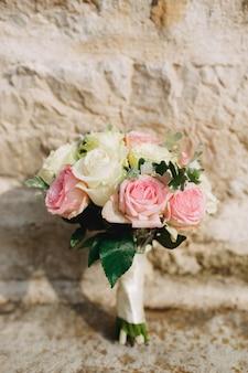 Bouquet da sposa di rose bianche e rosa e artemisia con nastri bianchi vicino al muro di mattoni
