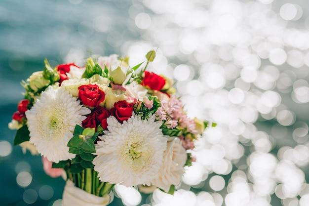 Bouquet da sposa di rose e crisantemi su uno sfondo textu