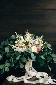 Bouquet da sposa di rose bianche e crema, rami di eucalipto delphinium e nastri bianchi