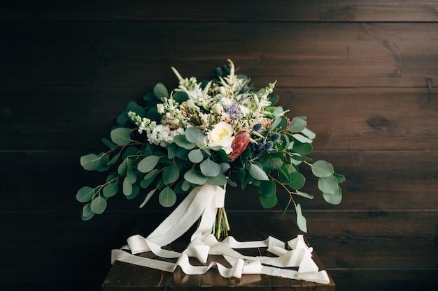 Bouquet da sposa di rose bianche e crema rami di eucalipto protea eryngium e delphinium