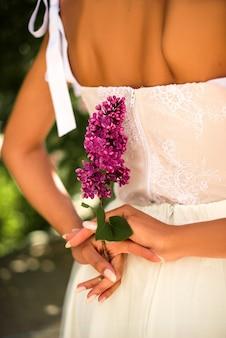 La sposa tiene in mano un ramoscello di lillà. nozze. dettagli. bokeh