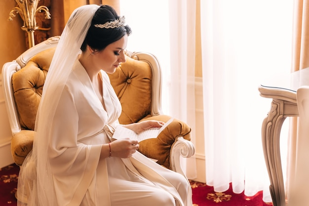La sposa in accappatoio si siede su una poltrona e legge una lettera. sposa con diadema e velo da sposa. profilo.