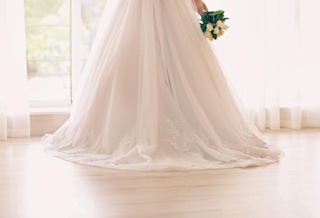 Sposa in un bellissimo vestito che tiene il bouquet da sposa