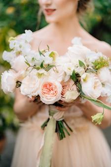 La sposa in un bel vestito tiene in mano un mazzo di fiori rosa