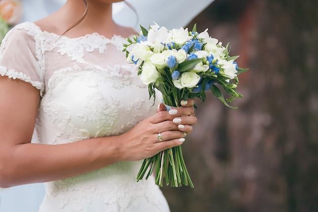 Una sposa in un bellissimo abito con un treno in possesso di un mazzo di fiori e verde