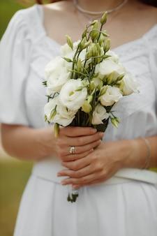 Una sposa in un bellissimo vestito con un treno che tiene un mazzo di fiori e vegetazione.