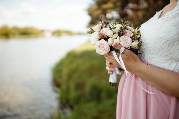 Sposa in un bel vestito con un treno in possesso di un mazzo di fiori e verde