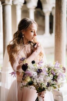 La sposa in un bellissimo vestito rosa tiene in mano un mazzo di fiori di campo