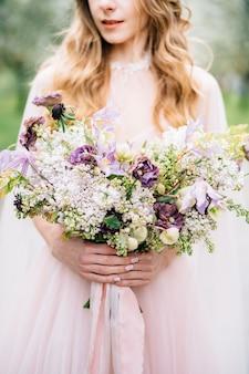 La sposa in un bel vestito rosa tiene un mazzo di fiori di campo nelle sue mani da vicino