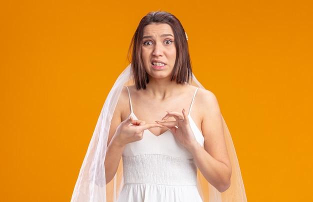 La sposa in un bellissimo abito da sposa sembra confusa e molto ansiosa