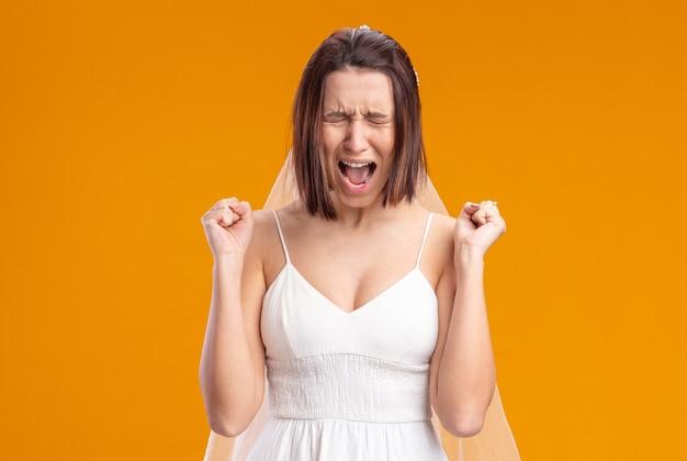 Sposa in bellissimo abito da sposa che grida di essere frustrata stringendo i pugni