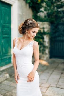 La sposa in un bellissimo abito bianco si trova vicino a un vecchio edificio con una porta verde nella città di perast