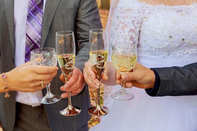 La sposa e le damigelle festeggiano e bevono champagne dai bicchieri