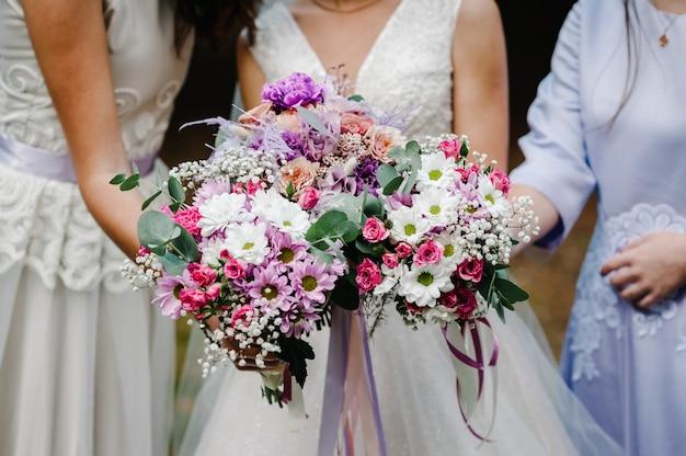 La sposa e le damigelle in un abito elegante sono in piedi e tengono in mano mazzi di fiori rosa pastello e verdi con nastro alla natura. giovani belle ragazze tiene un bouquet da sposa all'aperto.