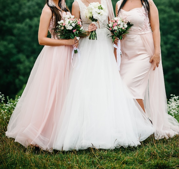 La sposa e le damigelle in un abito elegante sono in piedi e tengono per mano mazzi di fiori rosa pastello e verdi con nastro in natura. le giovani belle ragazze tengono un bouquet da sposa all'aperto.