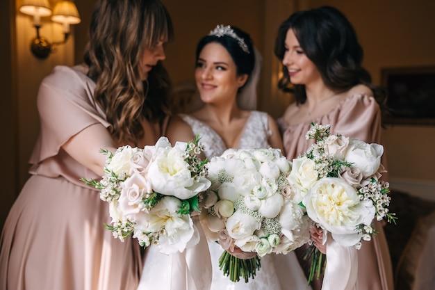 Sposa e damigelle d'onore che tengono i mazzi e che esaminano la macchina fotografica. primo piano di bellissimi mazzi di rose bianche.