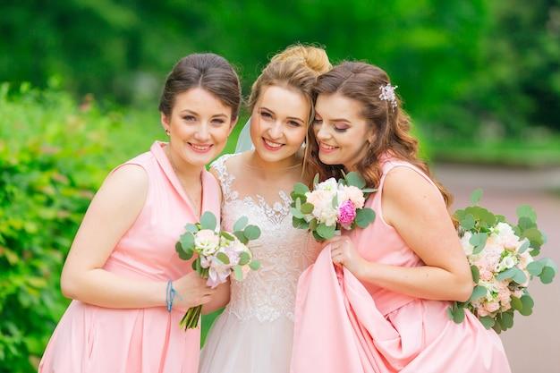 La sposa e le damigelle in abiti rosa si divertono e posano nel parco. ragazze che tengono i mazzi di nozze.