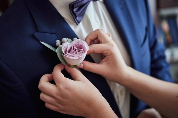 La sposa corregge il fiore all'occhiello dello sposo sulla giacca al loro matrimonio