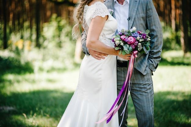 Sposa in abito e sposo in piedi in un giardino verde e con in mano un bouquet da sposa di fiori e verde. abbraccio di sposi sulla natura.