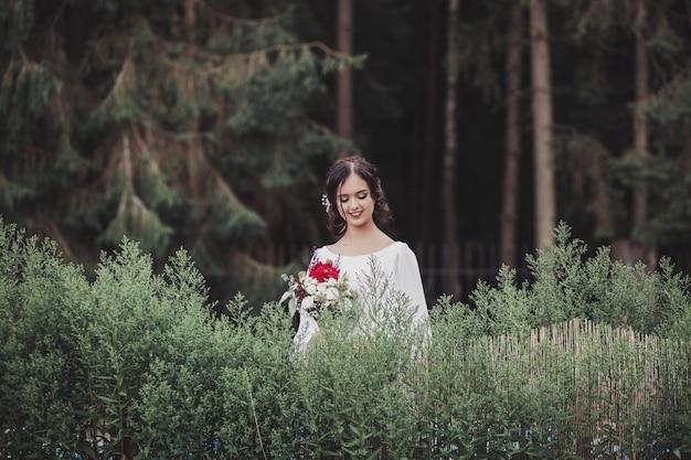 Sposa in un vestito che sta in un giardino verde