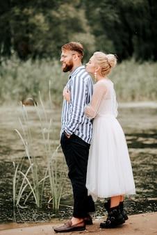 La sposa abbraccia dolcemente lo sposo da dietro sulla battigia. bellissimi sposi sullo sfondo del fiume.