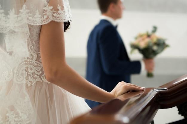 La sposa va incontro allo sposo. mano su una ringhiera di legno da vicino