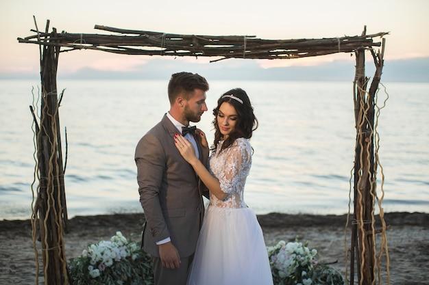La sposa e lo sposo sotto l'arco sulla spiaggia. tramonto, crepuscolo.