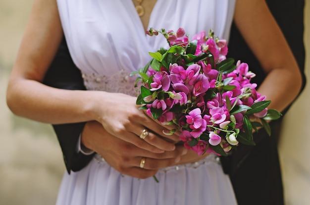La sposa e lo sposo stanno tenendo insieme il mazzo semplice rustico viola nelle mani. foto soleggiata e luminosa con fedi nuziali e braccia. abito bianco elegante e abito da sposa blu intenso.
