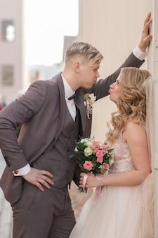 La sposa e lo sposo stanno parlando in piedi vicino all'edificio della città. feste ed eventi