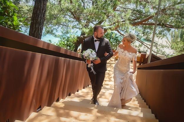 La sposa e lo sposo salgono le scale di struttura. felice giovane famiglia. l'uomo e la donna si amano. messa a fuoco selettiva. immagine diagonale. ragazzi fantastici. le coppie mostrano le emozioni. bionda con gli occhi azzurri