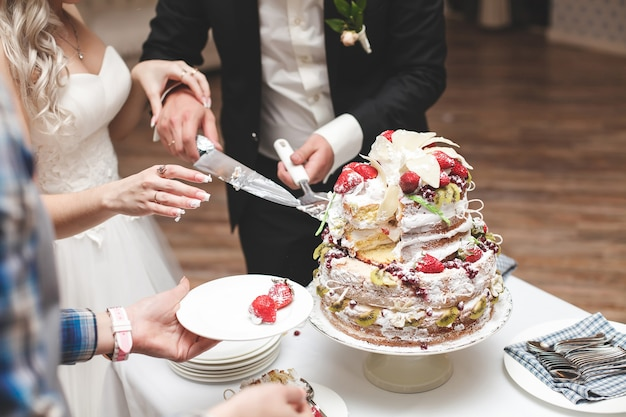 La sposa e lo sposo tagliano la torta nuziale.
