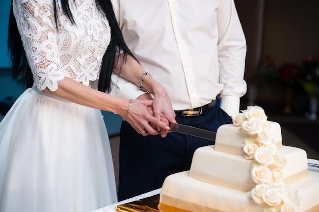 La sposa e lo sposo tagliano la torta nuziale