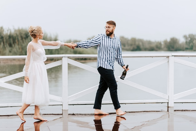 Gli sposi ballano a piedi nudi e si divertono sulla banchina in riva al fiume.