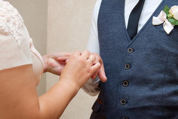 La sposa e lo sposo si vestono a vicenda con gli anelli di nozze alla cerimonia di registrazione del matrimonio.