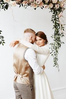 La sposa e lo sposo si abbracciano sotto un arco di fiori Foto Premium