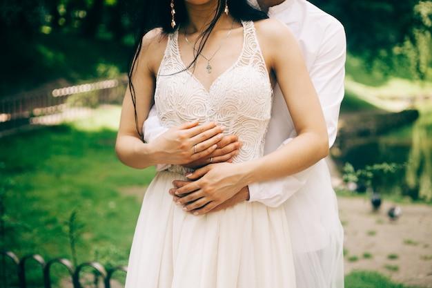 Le mani dello sposo e della sposa si chiudono su nel giorno soleggiato nel parco
