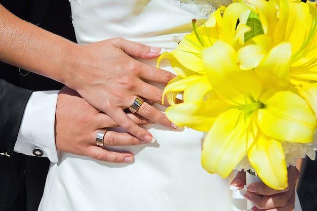 Mani degli sposi con fedi nuziali e bouquet