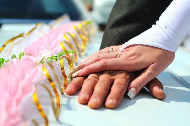 Mani dello sposo e della sposa con fedi nuziali