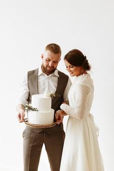 Gli sposi tengono una torta nuziale splendidamente decorata