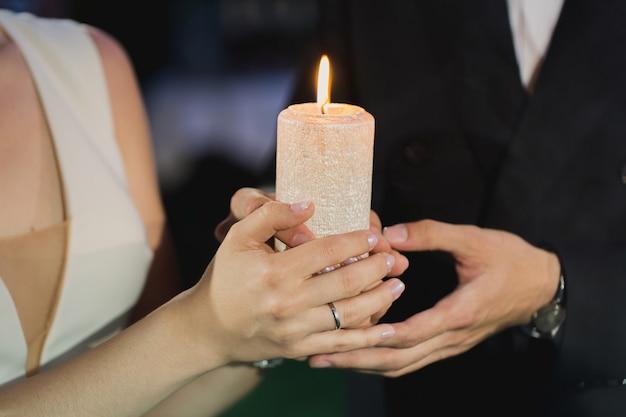 La sposa e lo sposo tengono una candela nelle loro mani