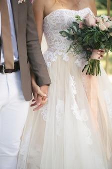 Gli sposi si tengono per mano. la sposa tiene in mano un mazzo di fiori.
