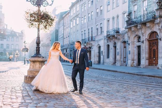 La sposa e lo sposo si tengono per mano e si guardano. passeggiare per la piazza della città vecchia.